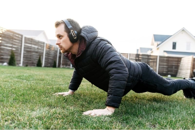 man doing calesthentics outside on the grass