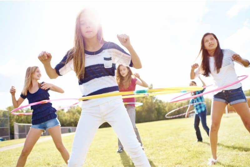 group of young girls doing hulahoops outside on the grass