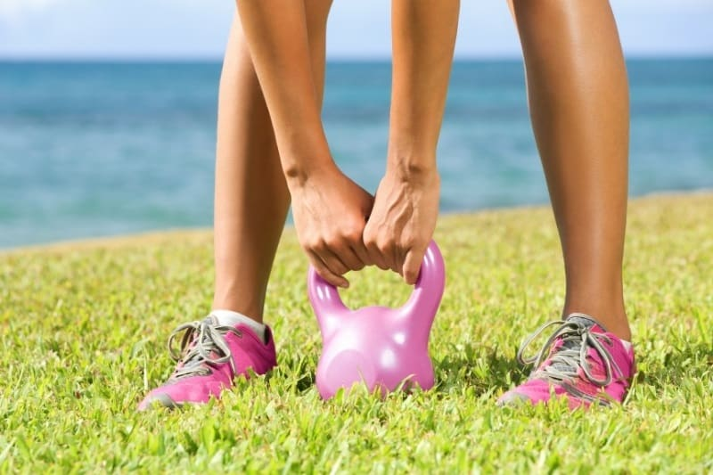 lady with pink sneakers picking up a pink kettlebell from the grass by the ocean