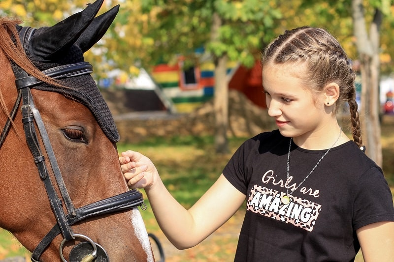young girl bonding with a horse in an equine therapy session