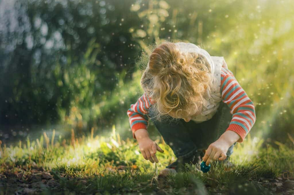 child hunting for items in nature on a scavenger hunt - a super fun nature activity for kids