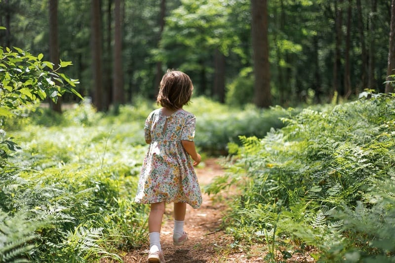 young child in a floral dress running on a path in the woods