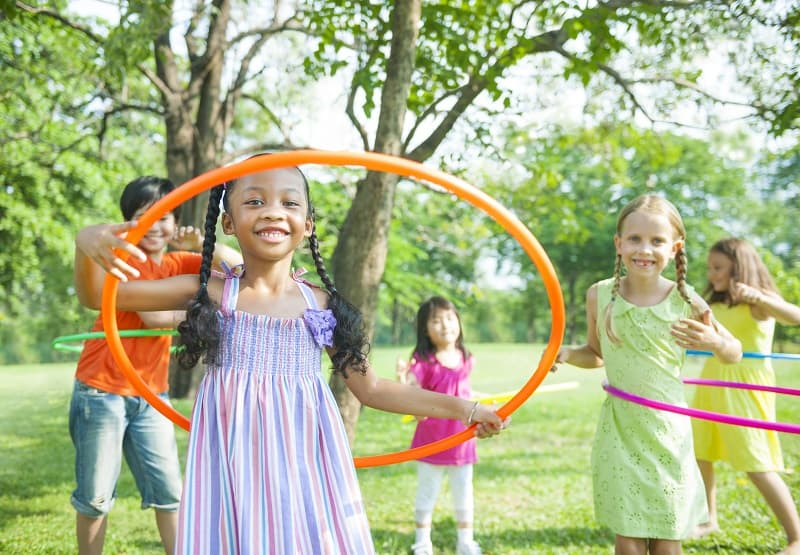 group of school age children playing outside with hoola hoops