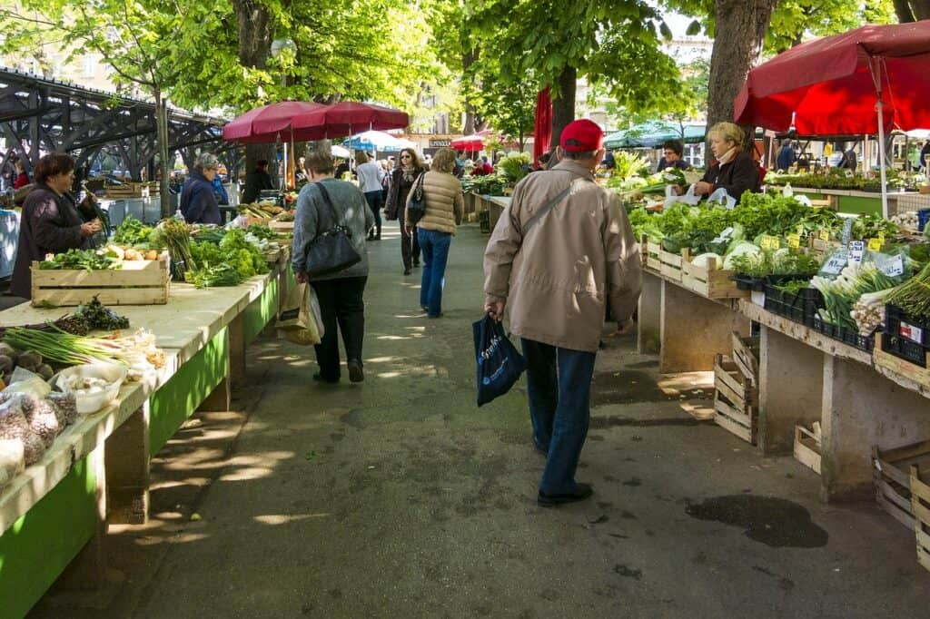 farmers market with red umbrellas and tables of fresh vegetables