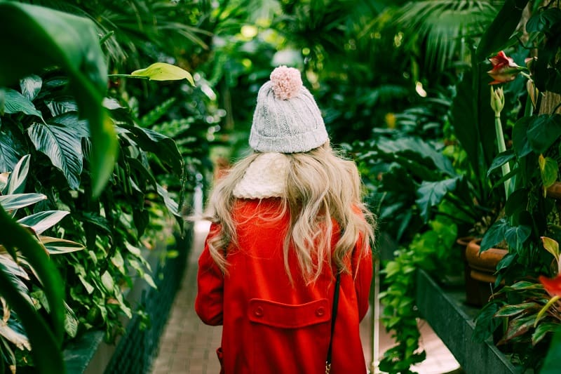 girl in a red coat walking through a botanical garden