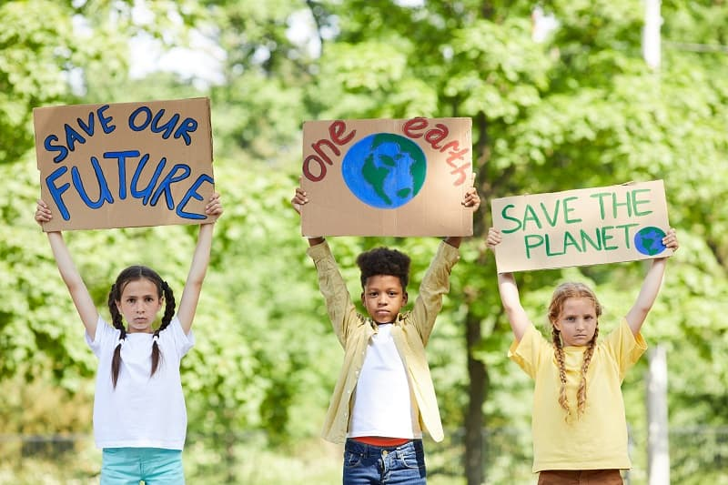 young children holding signs to save the plant and our earth