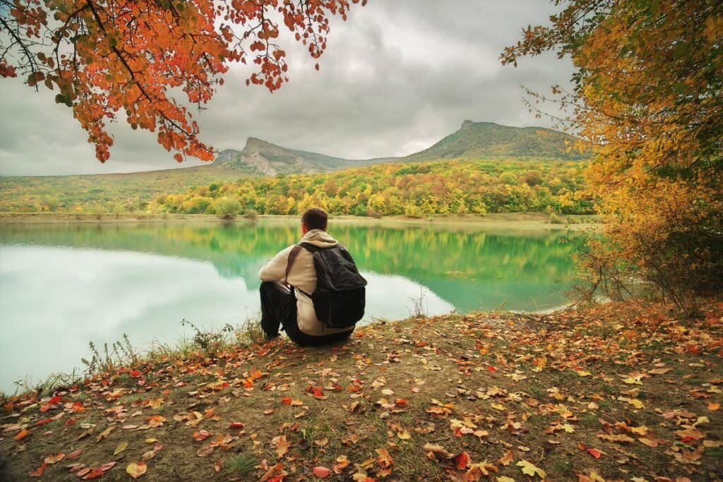 man sitting with a backpack in the autumn looking over a pond and mountains in the background