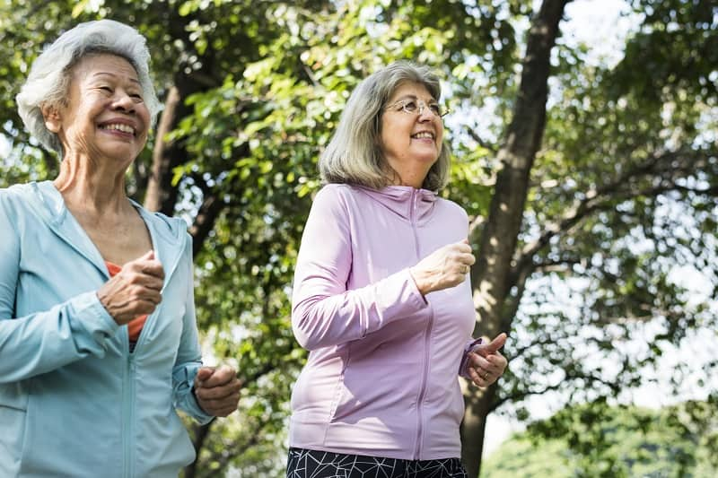 two happy seniors speed walking in nature