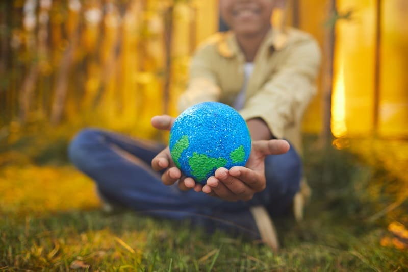 child holding a miniature world in his hands that represents caring for the earth
