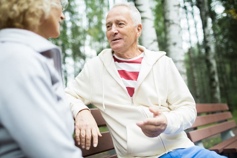 therapist talking to patient on a park bench outdoors - a form of ecotherapy