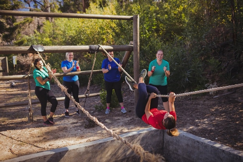 group of women encouraging each other through a ropes course - a great place to practice adventure therapy