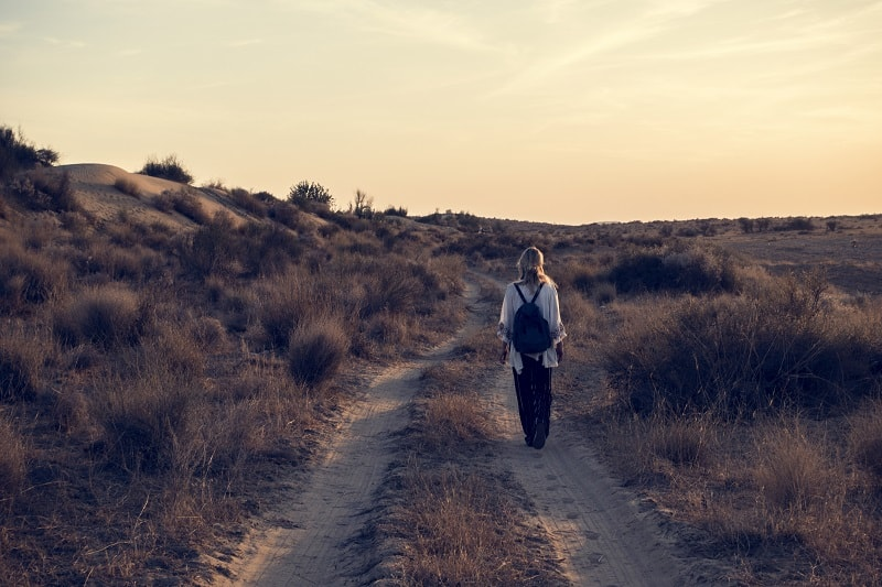woman walking alone in the desert with a backpack during a wilderness therapy retreat in a remote location to practice this solo form of ecotherapy
