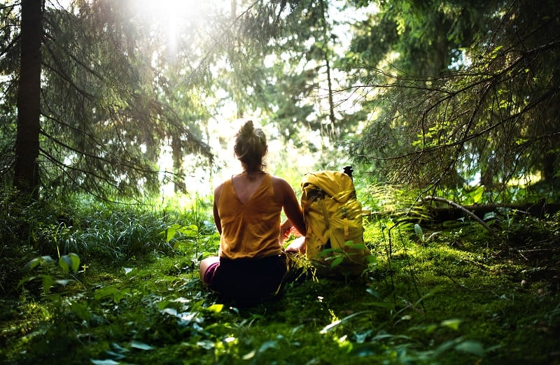 woman sitting in the middle of a forest meditating to reduce stress