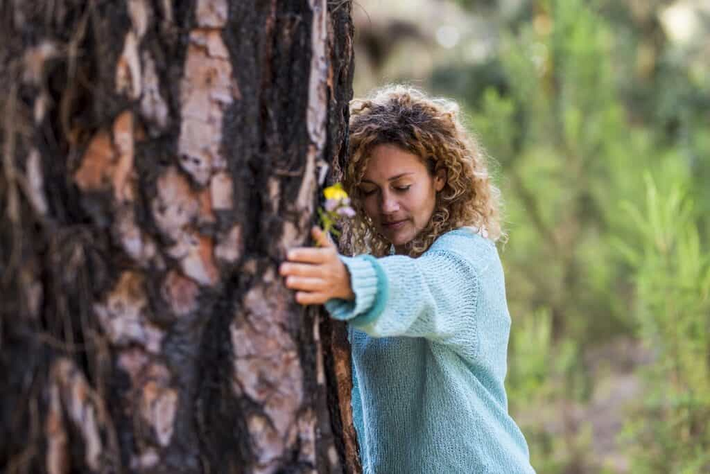 woman with her eyes closed touching a tree to absorb its energey, engaging in forest therapy an immersive type of ecotherapy activity