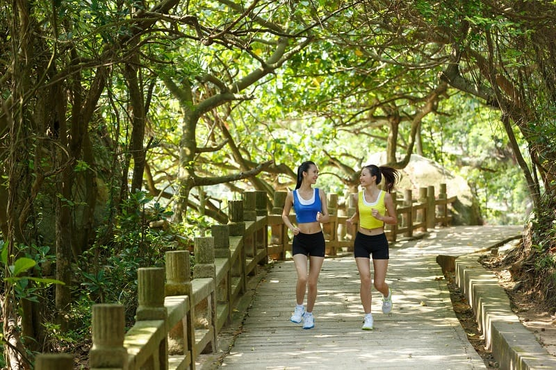 two young women jogging on a trail with trees in the background