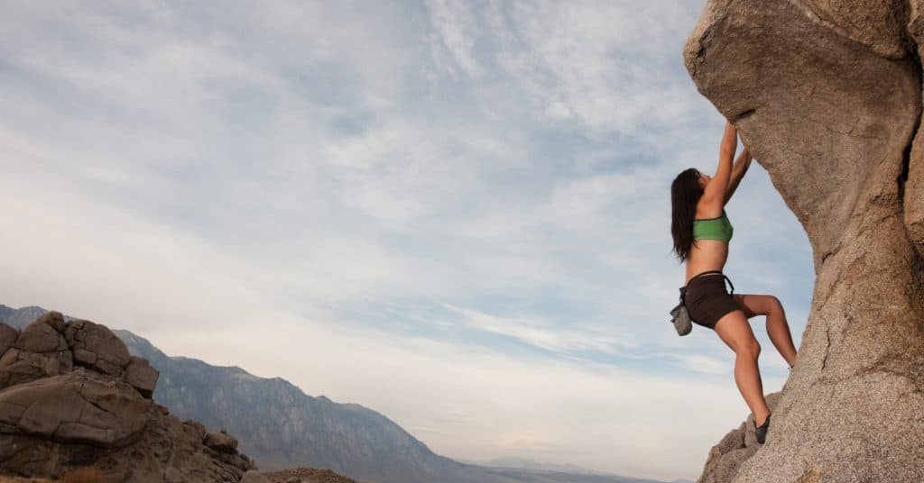 Woman rock climbing for adventure therapy