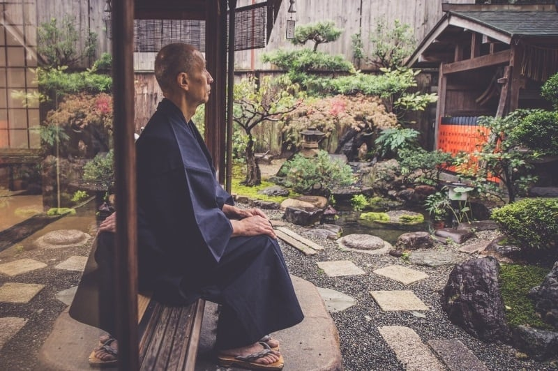 japenses man sitting overlloking his meditation garden