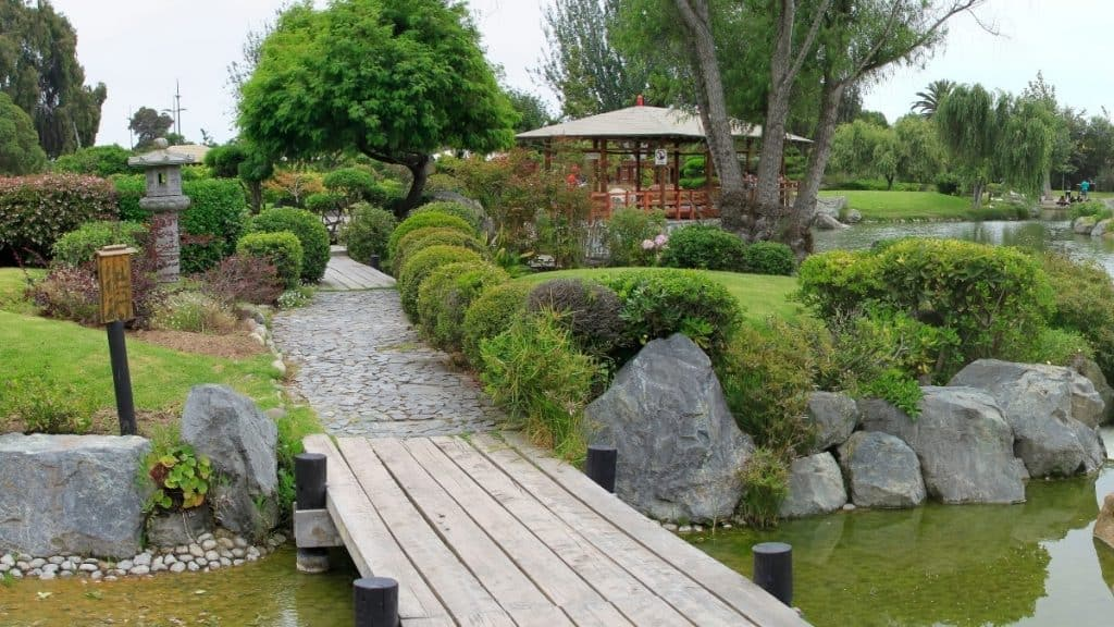 japanese inspired meditation garden with bridge covered structure plants and pretty design elements throught