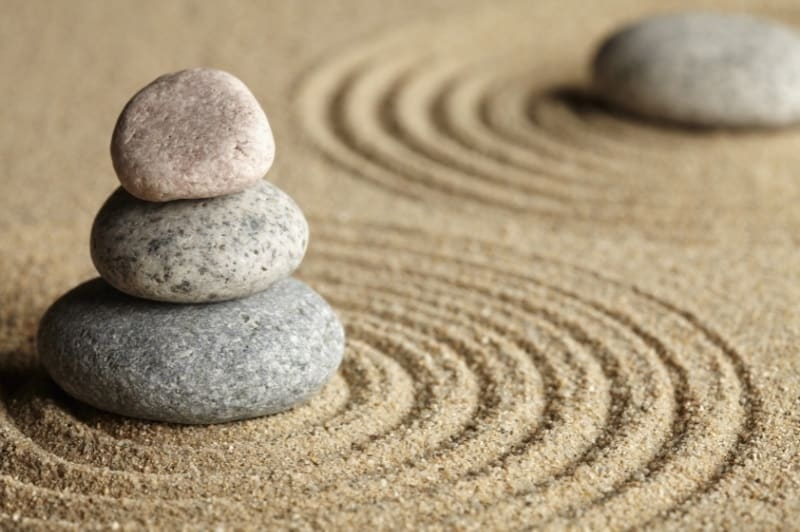 zen rocks piled in a tower in a sand meditation garden
