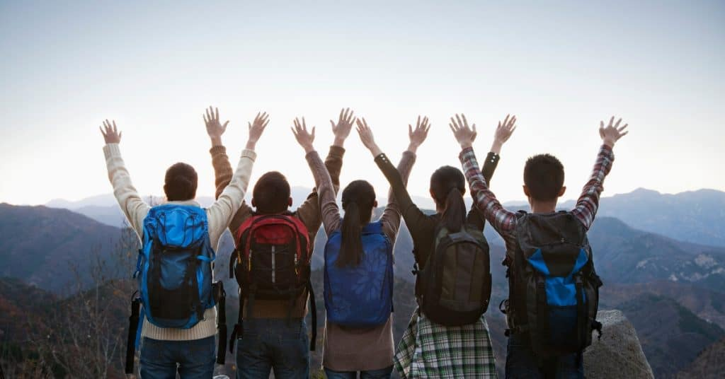 Group with their hands raised and backpacks on looking out