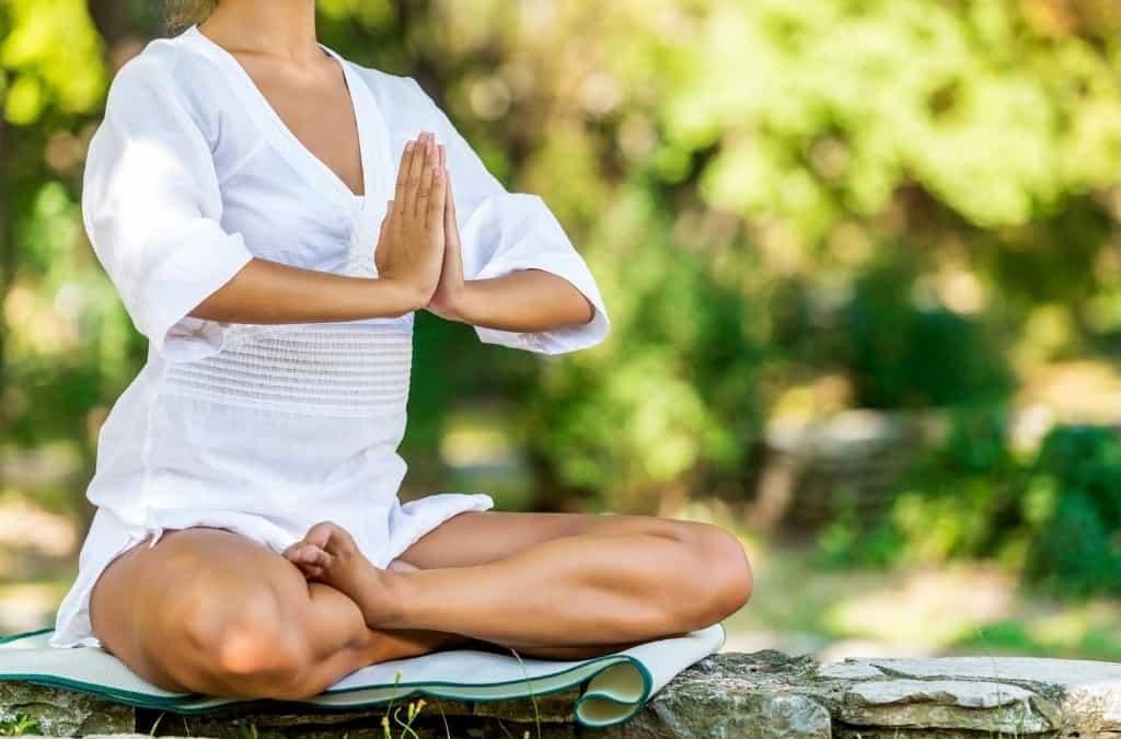 woman in a mediation pose outside in your backyard mediation garden