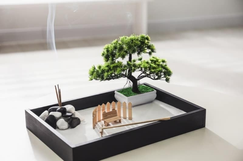 small zen garden with rocks, sand, rake, small bench and tree
