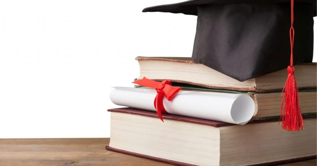 Graduation hat, diploma and books on a table