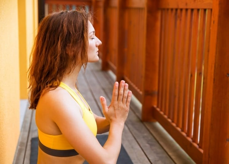 woman meditating in private location sheltered by a fence