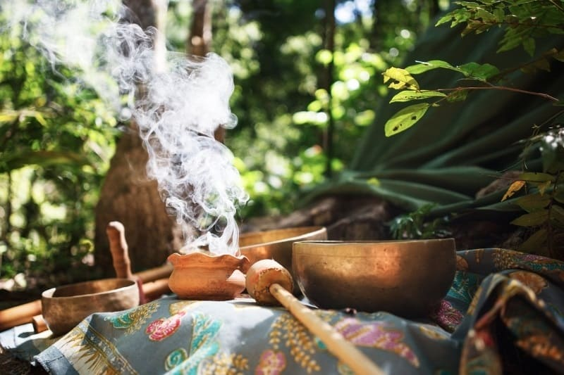 the healing tools of ancient medicine setup on a table in the forest - copper bowls, insense burning and drums