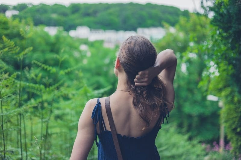 woman looking out over a sea of nature and green trees with a town just visible in the distance