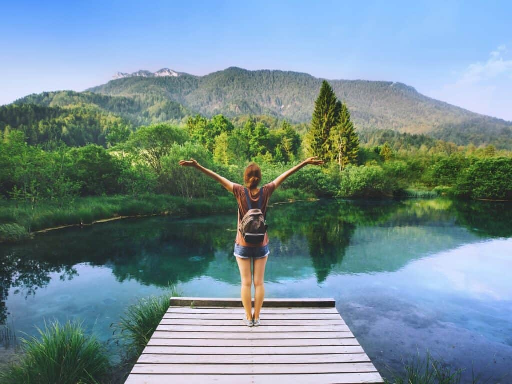 Girl with her arms up looking over a pond and mountains