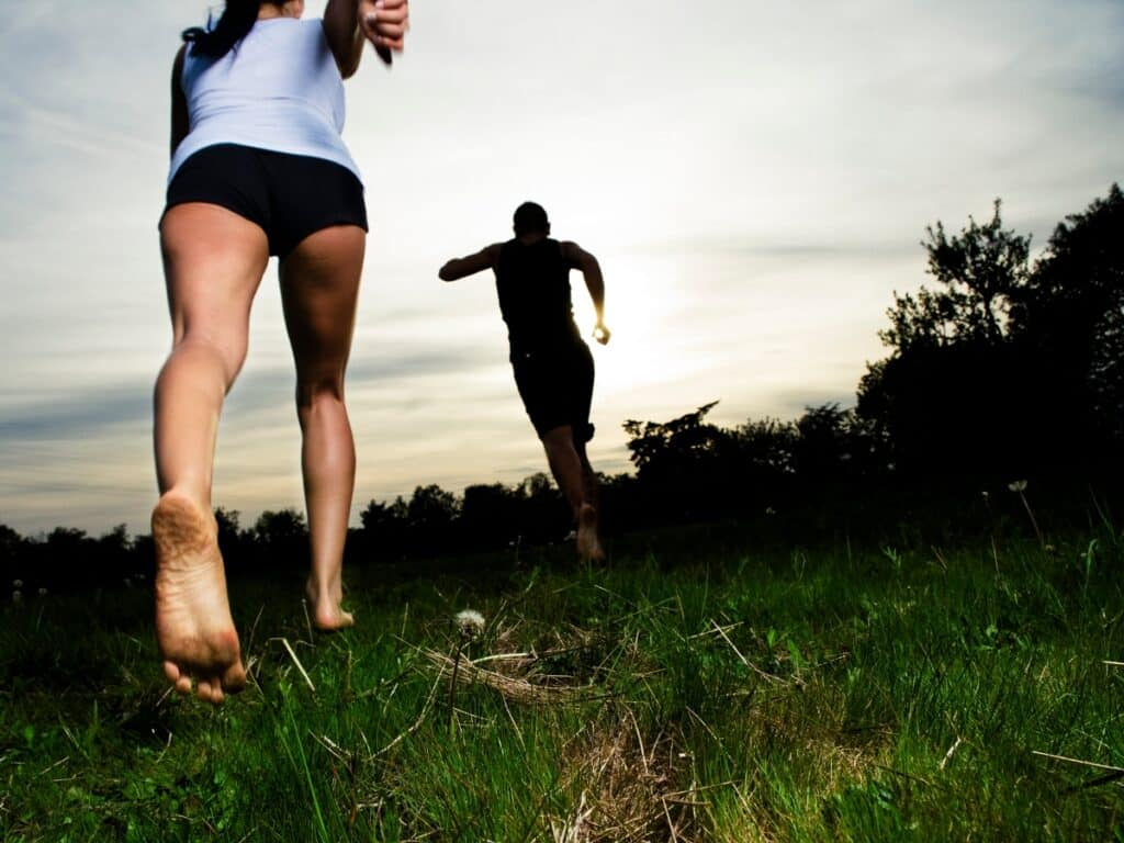Two people barefoot running on a nature trail