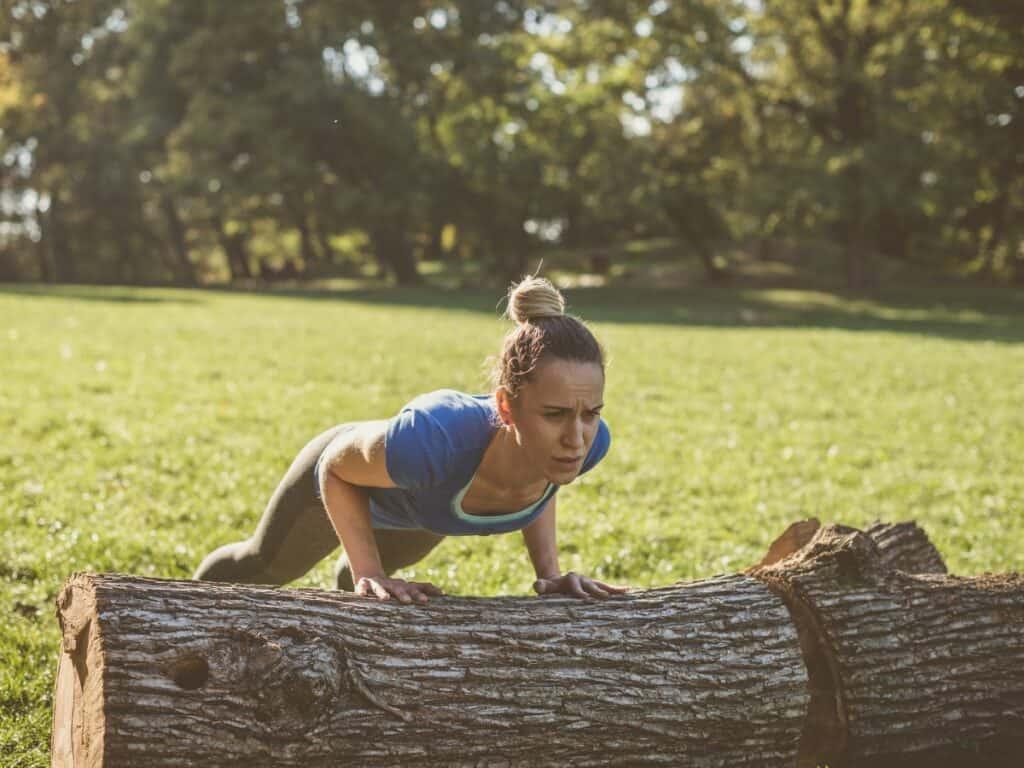 Woman doing pushups against a log