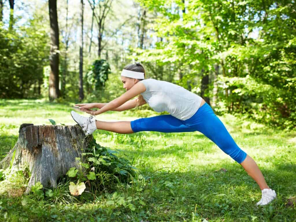 Woman stretching he leg on a tree stump for green exercise