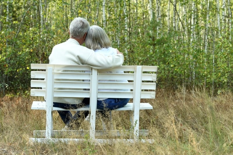 older couple sitting quietly on a park bench looking out into the trees