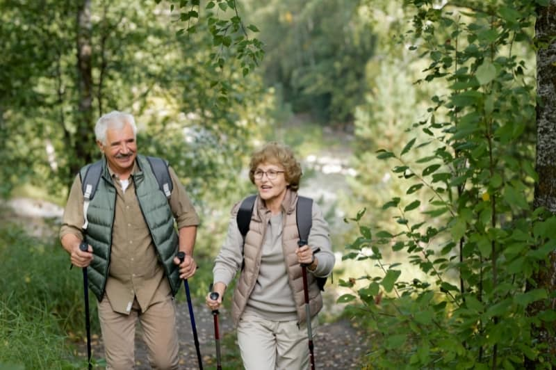 two older adults walking happily through the forest with walking sticks