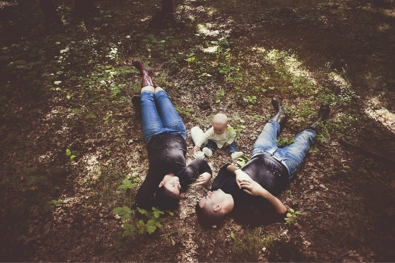 family lying on the forest floor with their young child