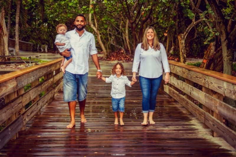 family holding handing walking on a wooden bridge with forest in the background