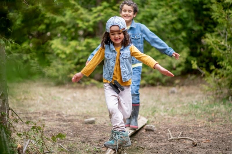 two happy kids balancing on a log in the woods