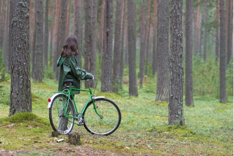 girl with a bike quietly observing the trees