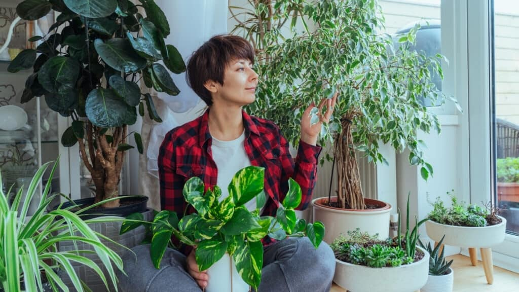 woman sitting by the window surrounded by houseplants