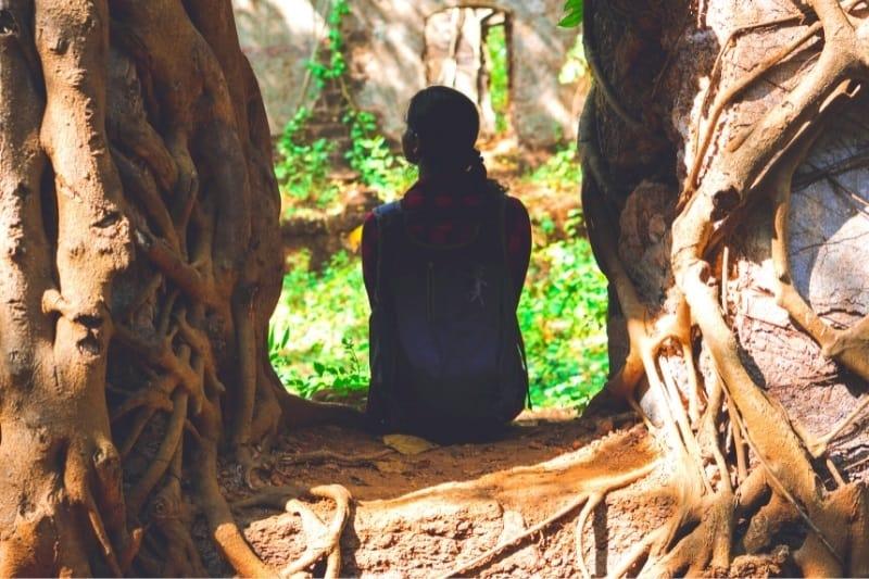 woman sitting beneath 2 giant trees