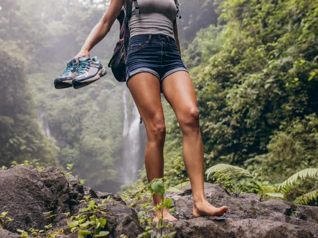 Girl getting the benefits of walking barefoot on the rocks