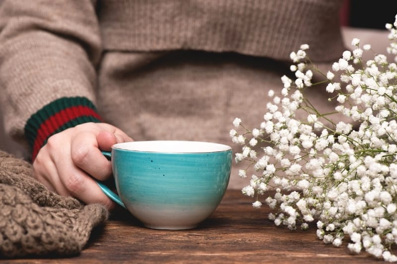 Cup of tea with blue mug and baby's breath flowers